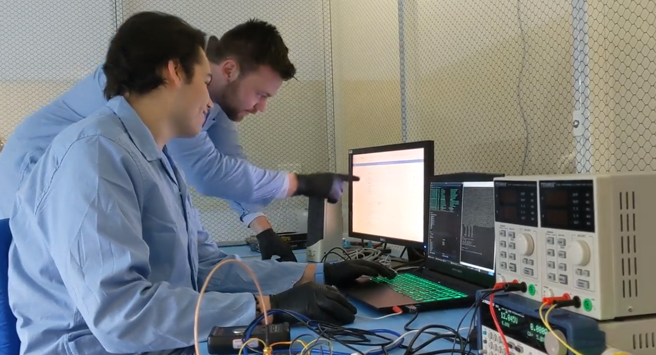 Engineers Daniel Wardle and James Hain surrounded by satellite electronics and checking data on the computer in the clean room
